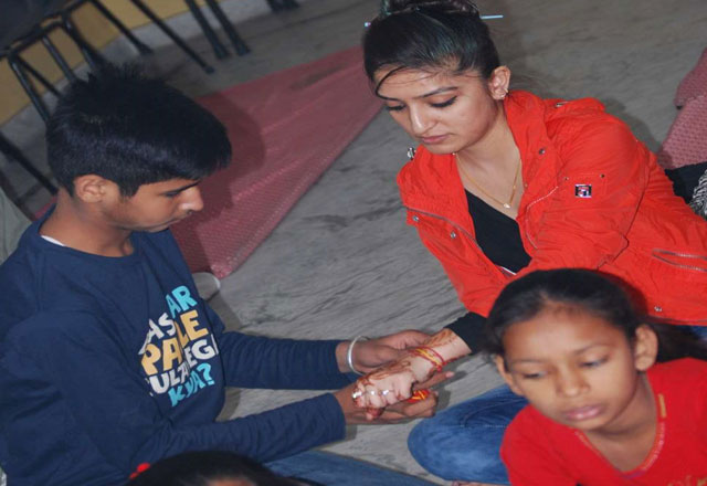 Most junior Adamya Veer is tieing Sacred Molly on the wrist of GG Alumini Deepika-1500